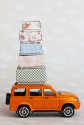 Orange toy car carries beautiful cardboard boxes on the roof. Relocation or house removal delivery service concept.