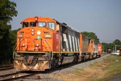 Orange train with stripes on rusty railroad tracks. Curvy splitting railroad tracks in the background.