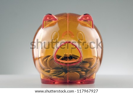 orange translucent piggy bank with coins inside