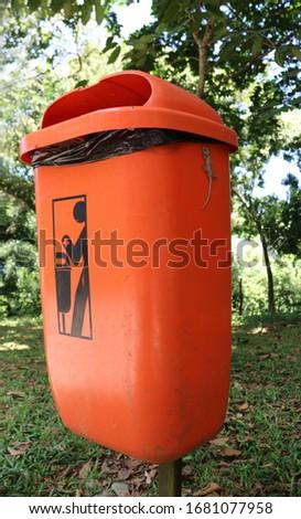 Orange trash can in Rio de Janeiro Park with a Lizard Foto stock ©