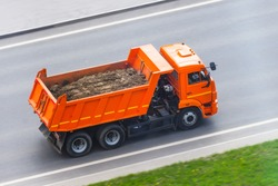 Orange truck dump with a load of soil in the body rides on the highway