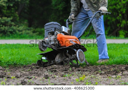 Orange two-wheel tractor grinds ground in the city center #408625300