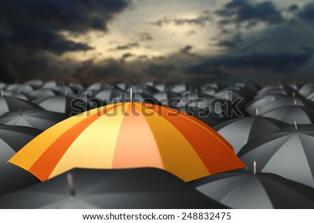 Orange umbrella in mass of black umbrellas