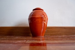 Orange Urn Leaning Against the White Wall