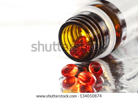 Orange vitamin pills and pill bottle