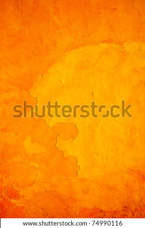 Orange wall with cracks and peeling paint.