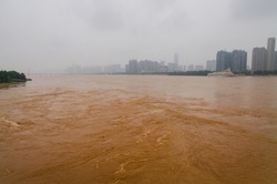 orange water in the river in Chinese city Changsha. city skyline on the background and dirty river on the front. river has strange and bright orange color