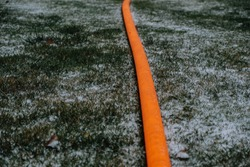 Orange water pipe in snow covered golf fields. Plastic water hose for pumping water making geometrical contrasting beauty. Pumping water for snow blower.