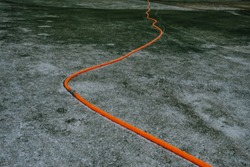 Orange water pipe in snow covered golf fields. Plastic water hose for pumping water making geometrical contrasting beauty. Pumping water for snow blower. Pipe connection and curve.