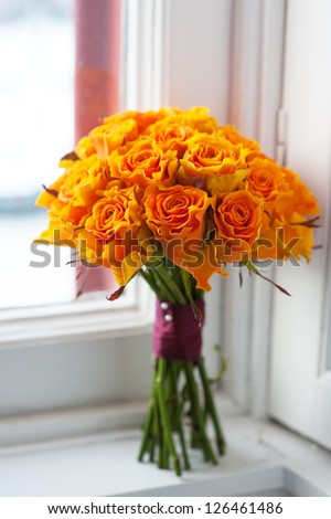orange wedding bouquet of roses on a windowsill by a window