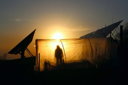 Orange western sun everywhere polyethylene tunnel in the form of a plastic greenhouse against the background of growing vegetables at sunset. contour of the solar station.Dark blue sky.