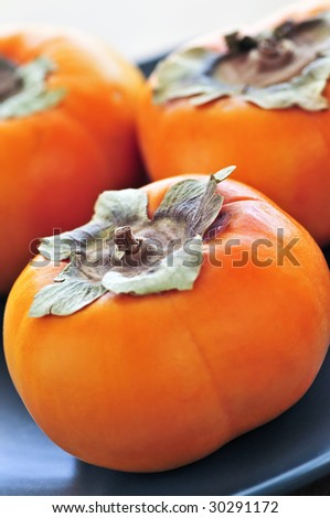 Orange whole ripe persimmon fruit on a plate