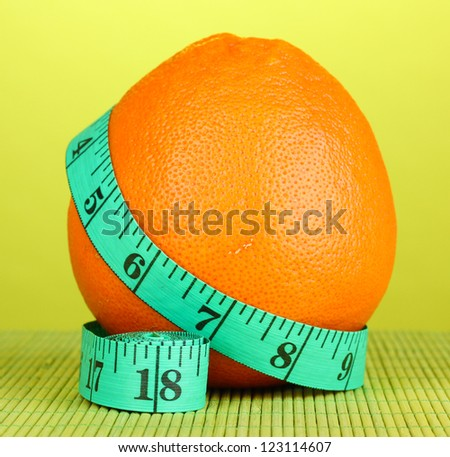 orange with measuring tape on green background