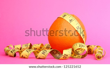 orange with measuring tape on pink background