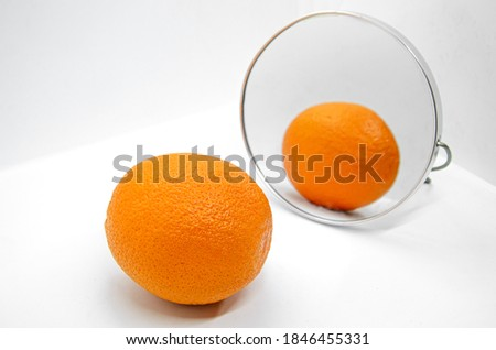 Orange with thick peel in cosmetic mirror on white background. Metaphor of cellulite treatment. Orange peel rough for symbolize of skin. Anti-cellulite creative concept. Selective focus on foreground Сток-фото ©