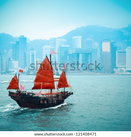 orange wooden sailboat sailing in victoria harbor at Hong Kong