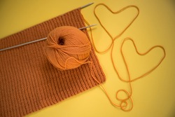 Orange wool thread and spokes with a knitted scarf on a yellow background. Flat lay.