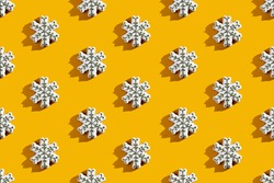 Orange Xmas background. Snowflake seamless pattern. New Year party ornament. White creative adornment minimalist symmetrical composition isolated on bright yellow.