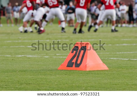 Orange yard marker on the sideline of a football field with a team playing in the background.  Shallow depth of field with the focus on the yard marker. - stock photo