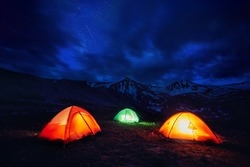 Orange yellow and green gloving tent at camping in the mountain gorge under night sky with stars