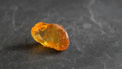 Orange yellow baltic amber stone on gray slate background , lit by the sun