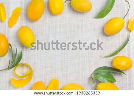 Orange-yellow maprang on the cloth lying around. Leave the middle for the text. Stok fotoğraf ©
