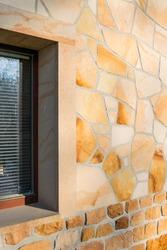 Orange-yellow sandstone facade.  Polish sandstone on the building. Sandstone texture.