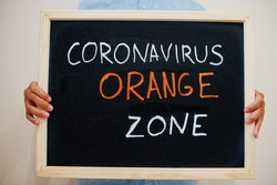 Orange zone. Coronavirus concept. Boy hold inscription on the board.
