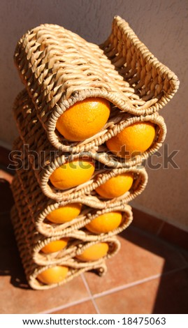 Oranges and grapefruits in wicker stand for wine bottles.