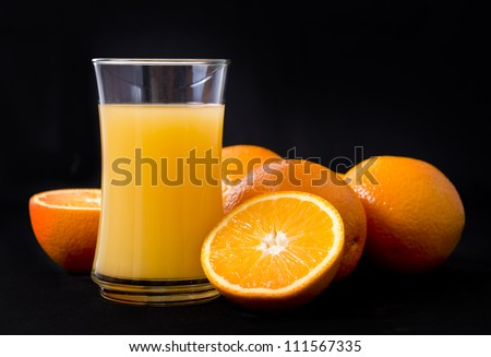 Oranges and juice on black background