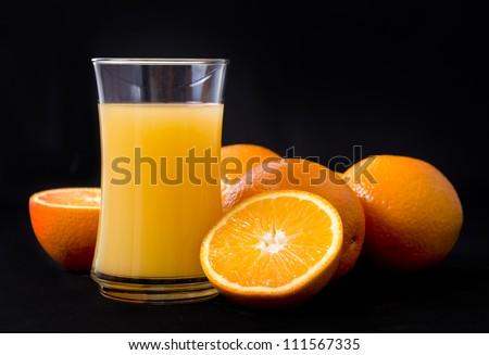 Oranges and juice on black background