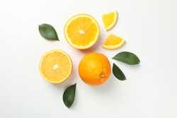 Oranges and leaves on white background, top view