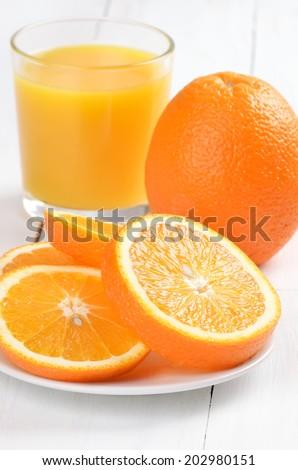 Oranges and orange juice on white wooden table