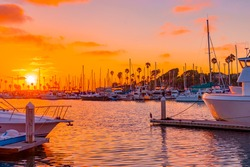 Oranges and pinks highlight all the boats,  rippled water and sky in Oceanside Harbor, near Carlsbad, California in Southern California.