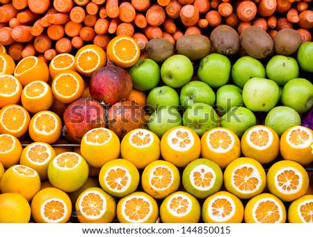 oranges, apples, kiwis, carrots and pomegranates presented at  the weekly fruit market