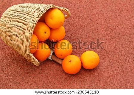 oranges fruits in wicker basket on Rubber floor