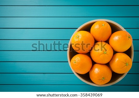 Oranges in bowl on wooden table