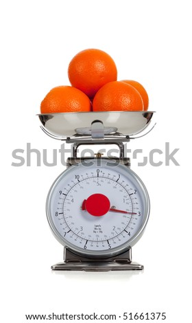 Oranges on a scale with a white background