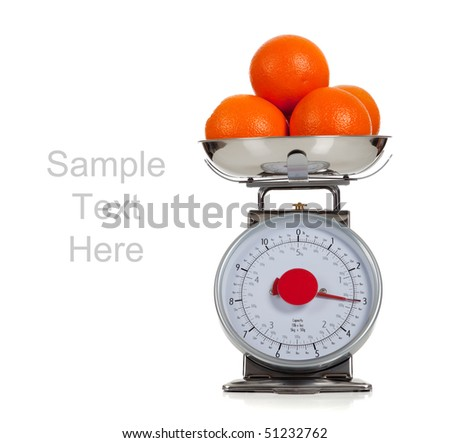 Oranges on a scale with a white background and copy space
