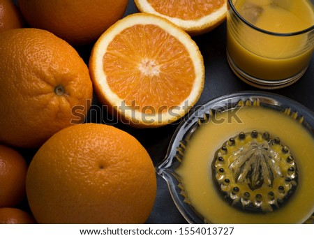 Oranges tangerines fresh fruit food and freshly squeezed healthy orange juice drink hand made with lemon squeezer and glass with juice and ice. Flat Lay #1554013727