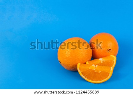 Oranges whole and sliced on solid blue background