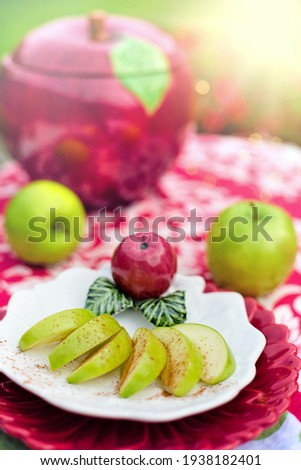 orchard with red apples, oranges on the plate, bright apples