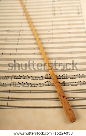 Orchestra conductor's baton resting on a music score