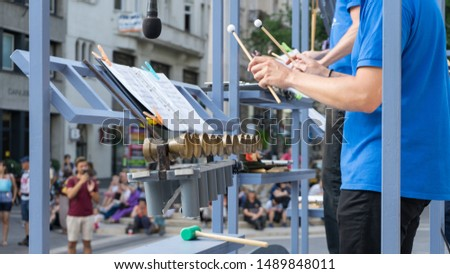Orchestra in Street performance in urban scene with pedestrians audience. Tourist attraction performing percussion event and music sheet #1489848011