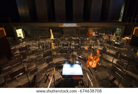 Orchestra pit with many seats and note stands, a conductors position and an intentionally motion blurred string instrument player visible.  #674638708