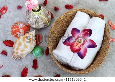 Orchid decorate on towel decorate with sea shell and dry rose, spa set.