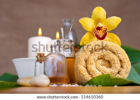 Orchid flower, towel, aroma oils, zen stones, over wooden surface
