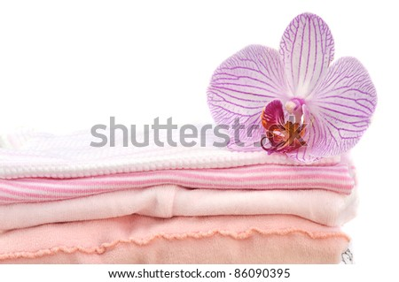 Orchid on a pile of folded pink laundry, isolated on white