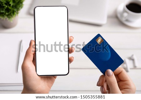 Order lunch online. Woman using credit card and cellphone with blank screen for ordering food delivery.