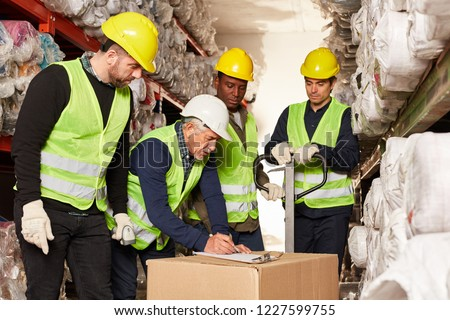 Order pickers and logistics workers control delivery in the shipping warehouse